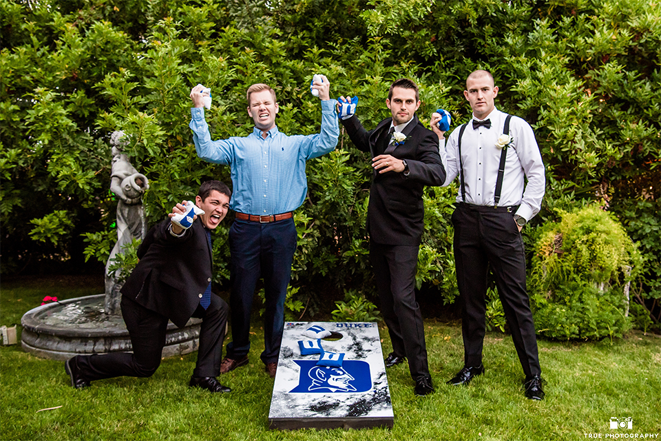 San diego wedding at green gables estate groom black shawl lapel tuxedo with matching vest and white dress shirt with long black skinny tie and white floral boutonniere with groomsmen bow ties and suspenders playing cornhole