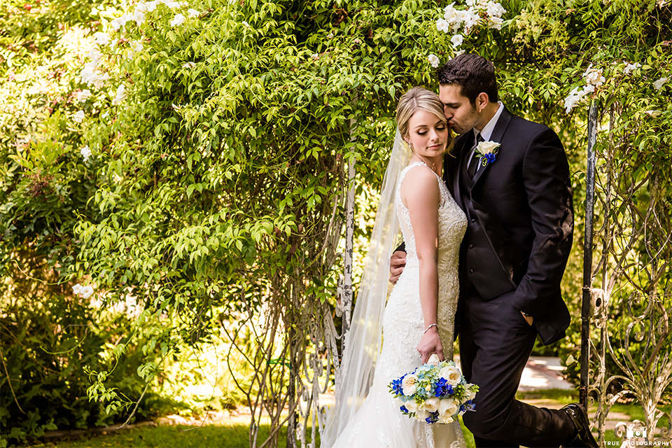 San diego wedding at green gables estate bride form fitting lace gown with a long train and high illusion neckline with long veil and groom black shawl lapel tuxedo with matching vest and white dress shirt with long black skinny tie and white floral boutonniere hugging and bride holding white and blue floral bridal bouquet
