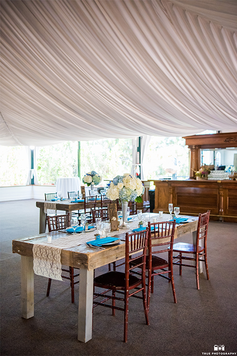 San diego wedding at green gables estate table set up light brown wood table with white and blue flower decor and white place settings with blue napkins and white candles with white draping on ceiling and hanging chandeliers