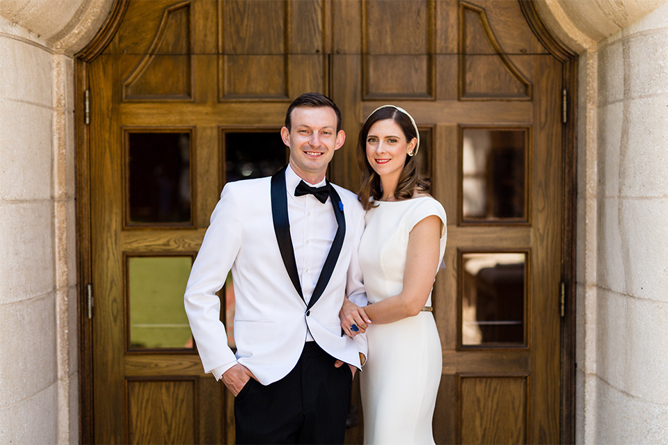 Orange county outdoor wedding at the green parrot villa bride form fitting white gown with a high neckline and crystal belt with short veil and groom white tuxedo jacket with black shawl lapel and black pants with white dress shirt and black bow tie standing and hugging