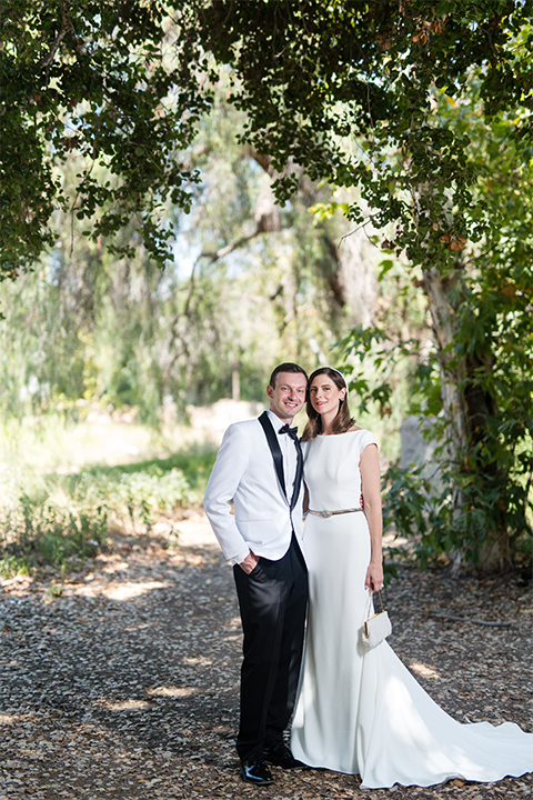 Orange county outdoor wedding at the green parrot villa bride form fitting white gown with a high neckline and crystal belt with short veil and groom white tuxedo jacket with black shawl lapel and black pants with white dress shirt and black bow tie standing and holding hands