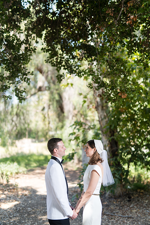 Orange county outdoor wedding at the green parrot villa bride form fitting white gown with a high neckline and crystal belt with short veil and groom white tuxedo jacket with black shawl lapel and black pants with white dress shirt and black bow tie standing and holdign hands