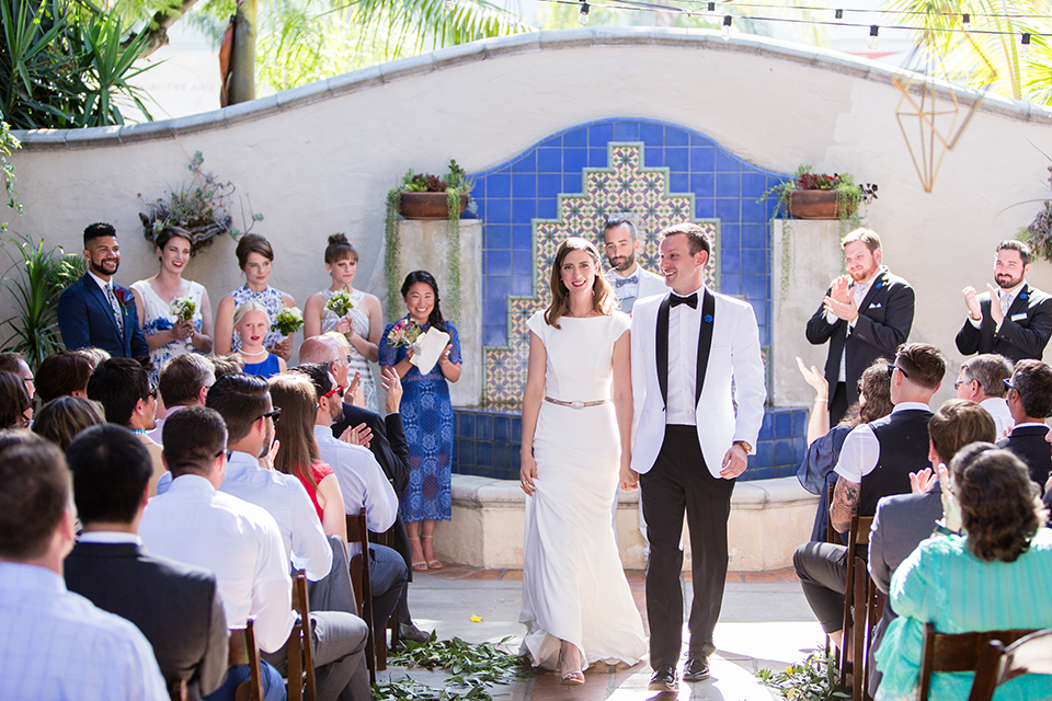 Orange county outdoor wedding at the green parrot villa bride form fitting white gown with a high neckline and crystal belt with short veil and groom white tuxedo jacket with black shawl lapel and black pants with white dress shirt and black bow tie holding hands and walking back down the aisle after ceremony