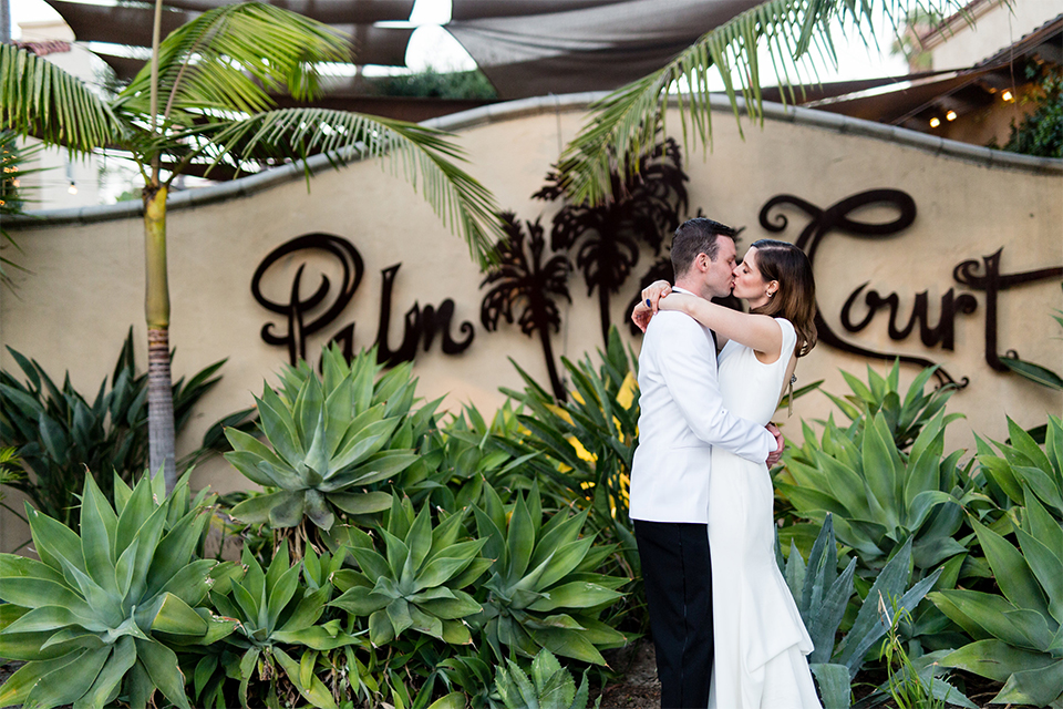 Orange county outdoor wedding at the green parrot villa bride form fitting white gown with a high neckline and crystal belt with short veil and groom white tuxedo jacket with black shawl lapel and black pants with white dress shirt and black bow tie hugging and kissing