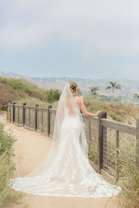 Los angeles wedding at los verdes golf club bride form fitting gown with lace detail and low back design with thin straps and long veil