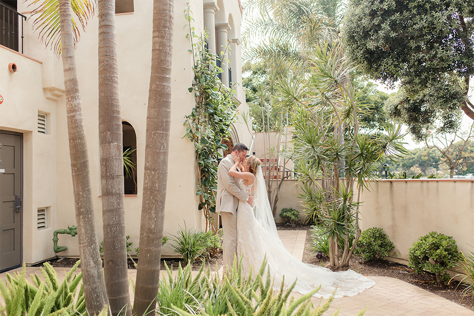 Los angeles wedding at los verdes golf club bride form fitting gown with lace detail and low back design with thin straps and long veil with groom tan notch lapel suit with matching vest and white dress shirt with matching tan bow tie and white pocket square with white and red floral boutonniere hugging and kissing