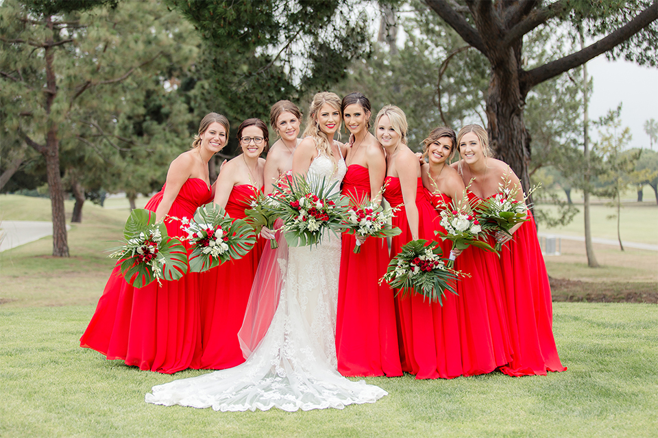 Los angeles wedding at los verdes golf club bride form fitting gown with lace detail and low back design with thin straps and long veil with bridesmaids long red dresses and white and red floral bouquets