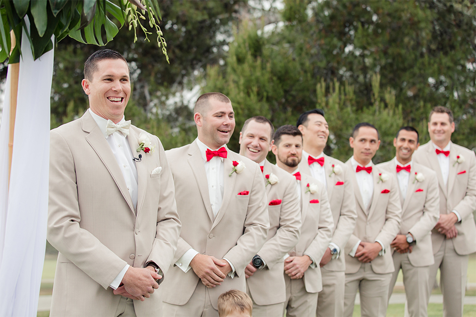 Los angeles wedding at los verdes golf club groom tan notch lapel suit with matching vest and white dress shirt with matching tan bow tie and white pocket square with white and red floral boutonniere with groomsmen tan suits with red bow ties