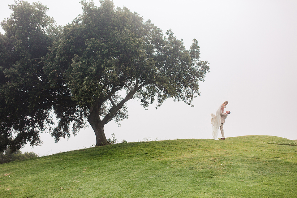Los angeles wedding at los verdes golf club bride form fitting gown with lace detail and low back design with thin straps and long veil with groom tan notch lapel suit with matching vest and white dress shirt with matching tan bow tie and white pocket square with white and red floral boutonniere kissing far away