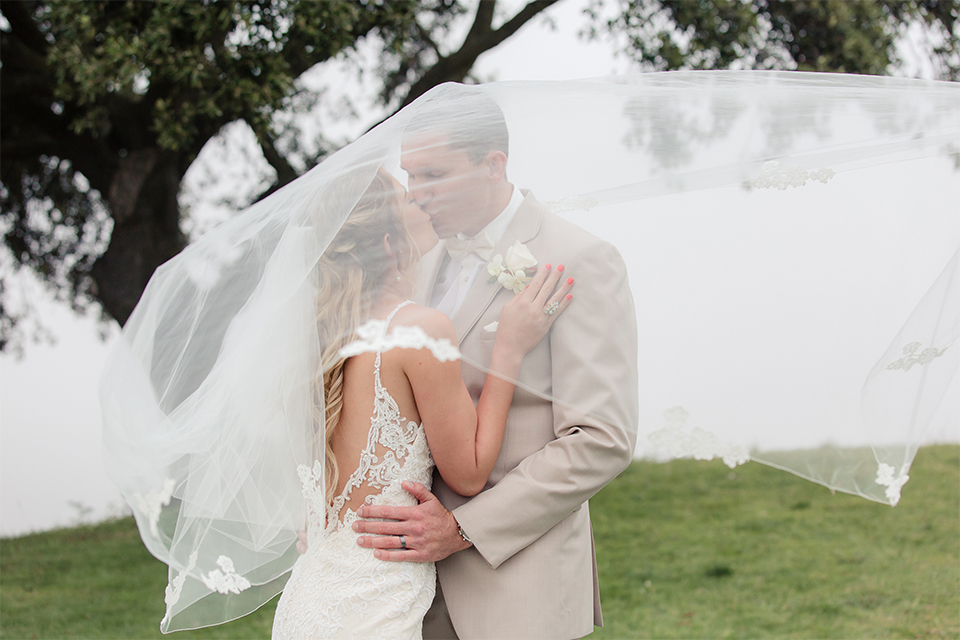 Los angeles wedding at los verdes golf club bride form fitting gown with lace detail and low back design with thin straps and long veil with groom tan notch lapel suit with matching vest and white dress shirt with matching tan bow tie and white pocket square with white and red floral boutonniere hugging and kissing under brides veil