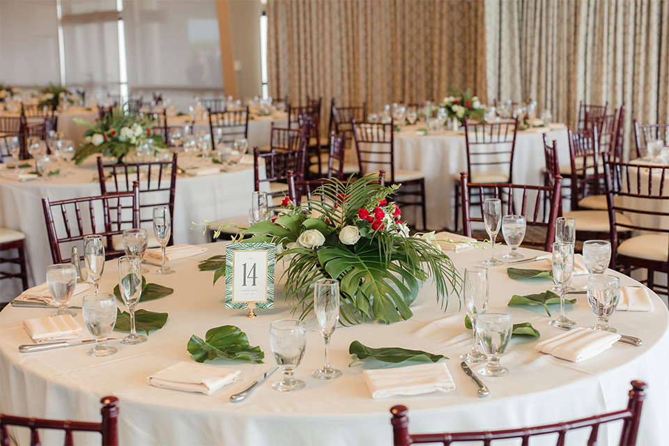 Los verdes golf club wedding table set up white table linens with dark chairs and white and green and red flower centerpiece decor with wine glasses and table numbers