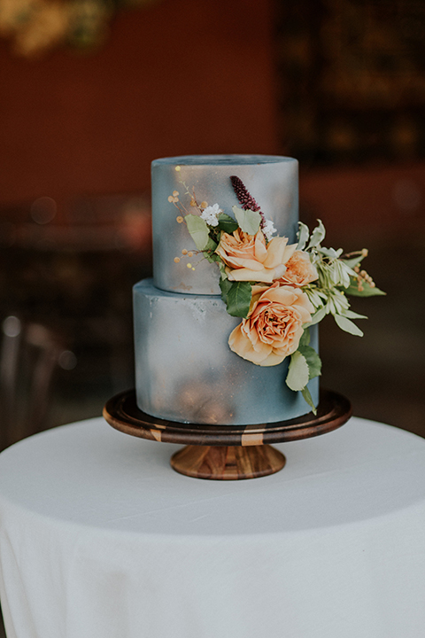 San diego outdoor wedding shoot at the zoo and safari park wedding cake two tier light blue wedding cake with light orange flower decor on side and brown cake stand with no cake topper on white table linen