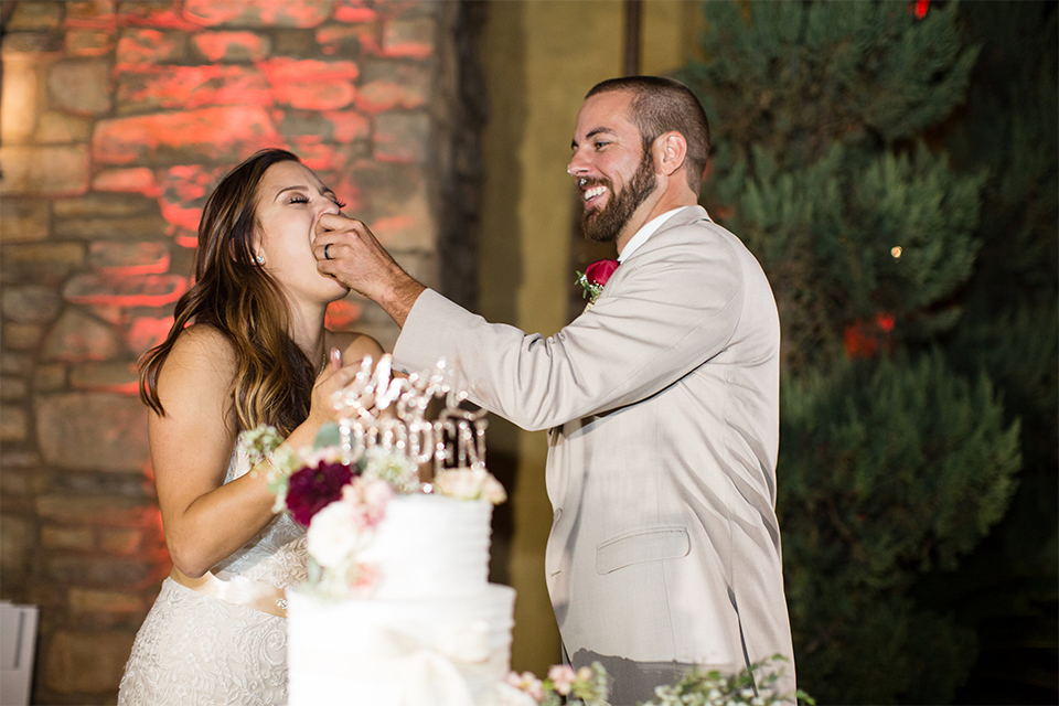 Temecula outdoor rustic wedding at lake oak meadows bride form fitting strapless gown with sweetheart neckline and lace detail with long veil and groom tan notch lapel suit with matching vest and white dress shirt and long white tie with red floral boutonniere feeding cake
