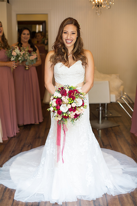 Temecula outdoor rustic wedding at lake oak meadows bride form fitting strapless gown with sweetheart neckline and lace detail with long veil with necklace holding white and red floral bridal bouquet with red ribbon decor
