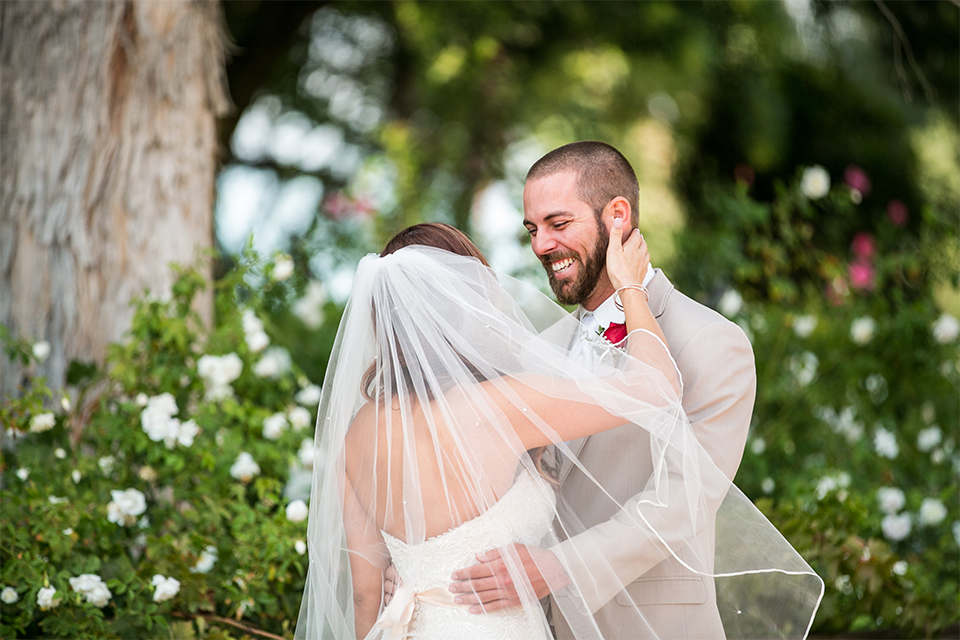 Temecula outdoor rustic wedding at lake oak meadows bride form fitting strapless gown with sweetheart neckline and lace detail with long veil and groom tan notch lapel suit with matching vest and white dress shirt and long white tie with red floral boutonniere hugging