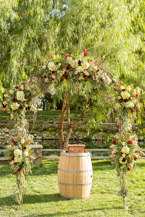Temecula outdoor rustic wedding at the lake oak meadows ceremony decor wine barrel with wood tree stump and black and white chalkboard design on the grass wedding photo idea for ceremony decor with floral arch with white and red flowers and greenery