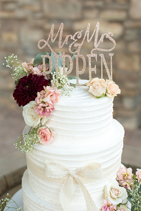Temecula outdoor rustic wedding at the lake oak meadows wedding cake decor two tier white wedding cake with white and red flower decor on top and calligraphy cake topper wedding photo idea for cake