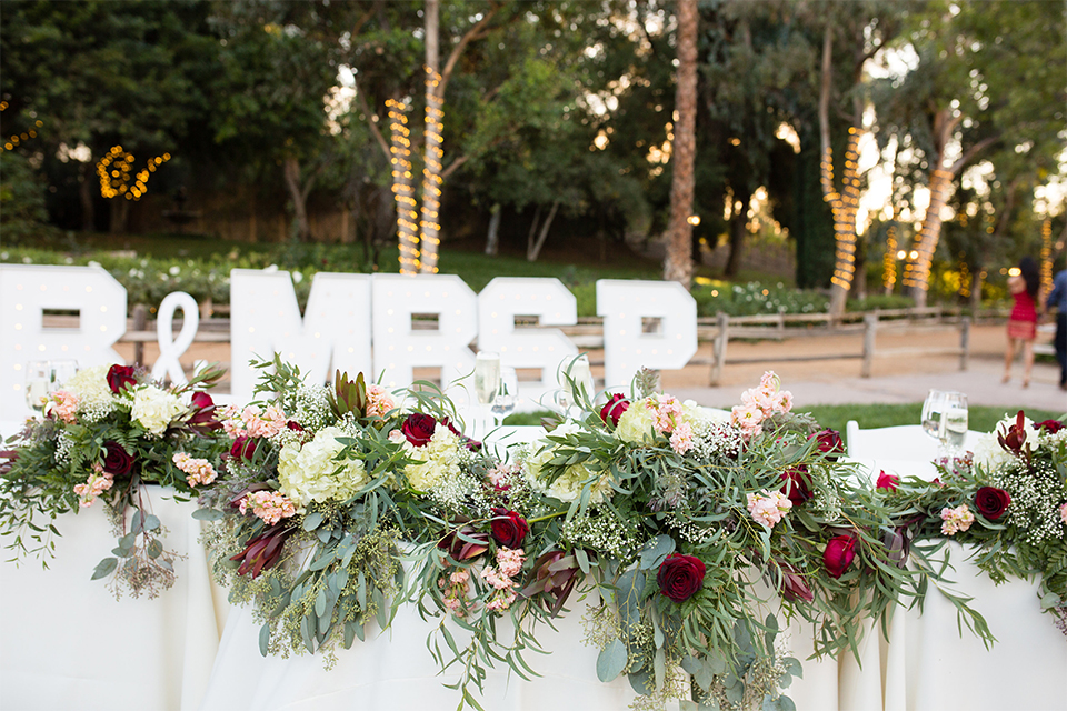 Temecula outdoor rustic wedding at the lake oak meadows table set up with white table linen and white and red flower decor with greenery florals and white initial letters with white place settings and gold table numbers