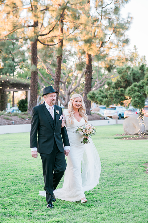 Orange county outdoor wedding shoot at turnip rose garden bride form fitting gown with lace detail and long sleeves with long veil and sweetheart neckline walking down the aisle with dad black tux