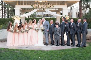 Orange county outdoor wedding shoot at turnip rose garden bride form fitting gown with lace detail and long sleeves with long veil and sweetheart neckline with groom heather grey notch lapel suit with matching vest and white dress shirt with long white tie and blush pink floral boutonniere kissing with wedding party bridesmaids long blush pink dresses with flower crowns and groomsmen charcoal grey suits with long blush pink ties