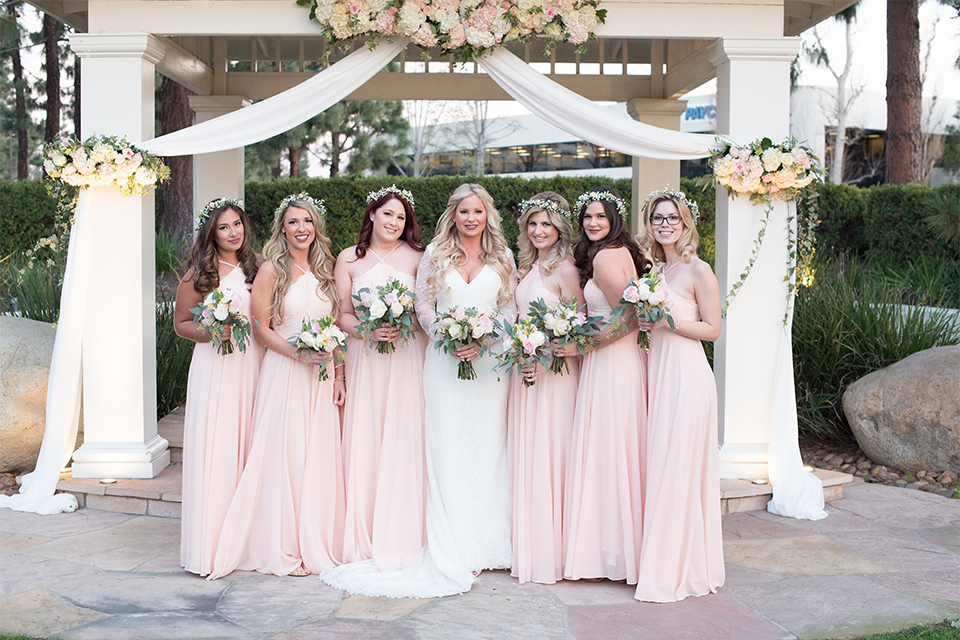Orange county outdoor wedding shoot at turnip rose garden bride form fitting gown with lace detail and long sleeves with long veil and sweetheart neckline holding white and green floral bouquet with bridesmaids long blush pink dresses with flower crowns holding white and green floral bouquets