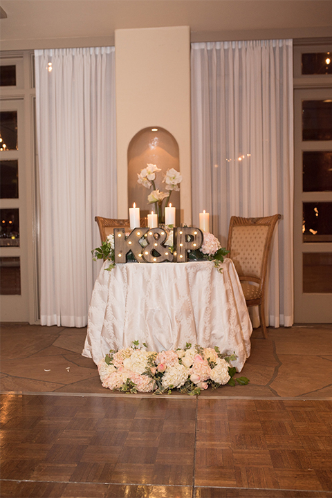 Orange county outdoor wedding at turnip rose garden table set up with white table linen and white flower decor with tall white candles and greenery floral decor with light up initials