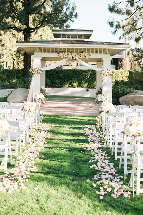 Orange county outdoor wedding at turnip rose garden ceremony set up on grass with altar and white chiffon with white and pink flower decor and white chairs with white flower petals along aisle wedding photo idea for ceremony