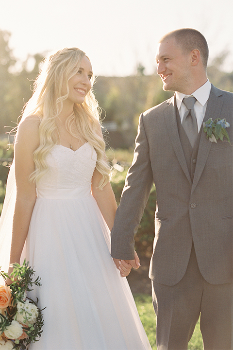 Southern california wedding at riverview free church bride strapless ball gown with a sweetheart neckline and tulle skirt with a long veil and braided hairstyle with groom grey notch lapel suit with matching vest and white dress shirt with long grey tie and light blue and green floral boutonniere holding hands
