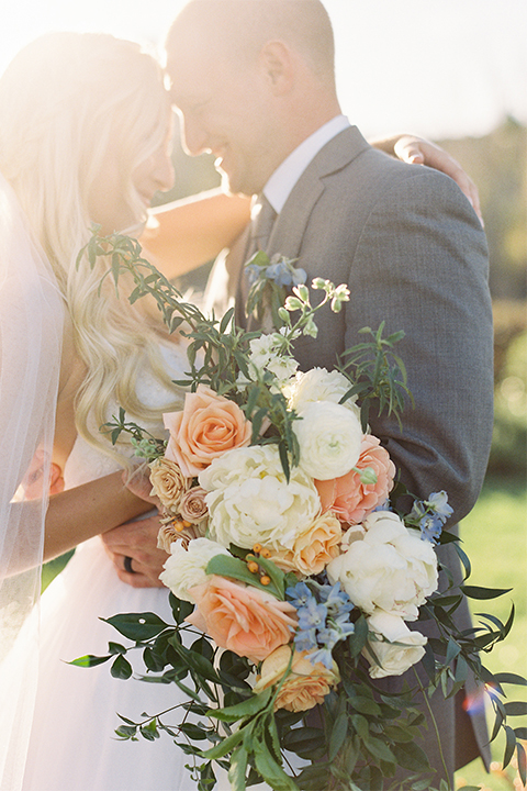 Southern california wedding at riverview free church bride strapless ball gown with a sweetheart neckline and tulle skirt with a long veil and braided hairstyle with groom grey notch lapel suit with matching vest and white dress shirt with long grey tie and light blue and green floral boutonniere hugging and bride holding white and orange floral bridal bouquet