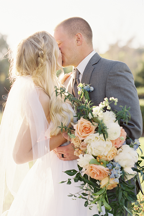 Southern california wedding at riverview free church bride strapless ball gown with a sweetheart neckline and tulle skirt with a long veil and braided hairstyle with groom grey notch lapel suit with matching vest and white dress shirt with long grey tie and light blue and green floral boutonniere hugging and kissing and bride holding white and orange floral bridal bouquet