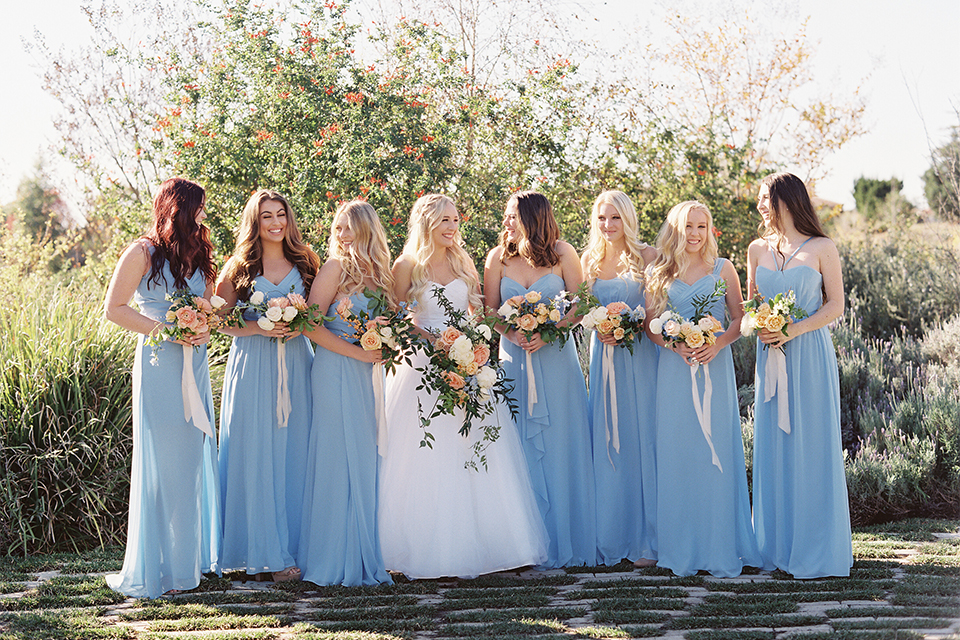 Southern california wedding at riverview free church bride strapless ball gown with a sweetheart neckline and tulle skirt with a long veil and braided hairstyle holding white and orange floral bridal bouquet with bridesmaids long light blue dresses with white floral bridal bouquets and ribbon decor