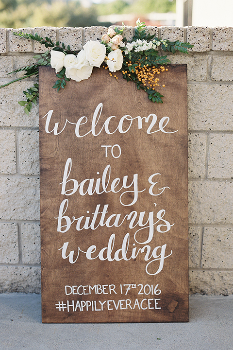 Southern california outdoor wedding at the riverview free church wedding welcome sign light brown wood sign with white calligraphy writing rustic decor with white and green flowers on top wedding photo idea for decor