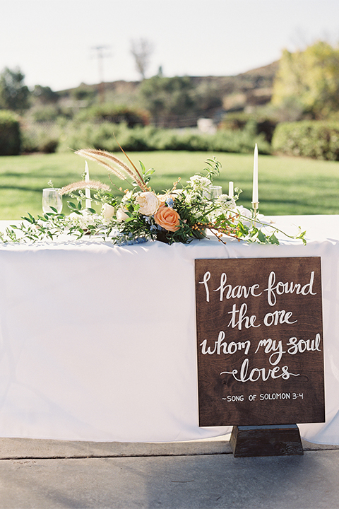 Southern california outdoor wedding at the riverview free church wedding welcome sign light brown wood sign with white calligraphy writing rustic decor with white and green flowers on top with table white linen and white place settings with tall white candles and gold holders with light orange and white flower centerpiece decor with gold vases and gold silverware