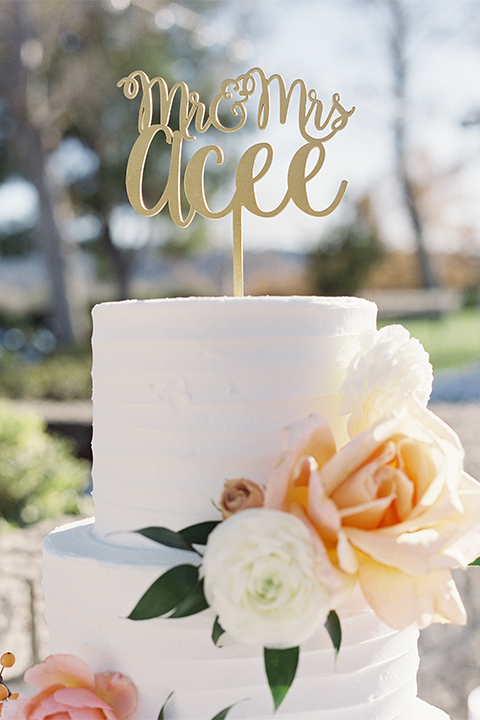 Southern california outdoor wedding at the riverview free church wedding welcome sign light brown wood sign with white calligraphy writing rustic decor with white and green flowers on top with table white linen and white place settings with tall white candles and gold holders with light orange and white flower centerpiece decor with gold vases and gold silverware with three tier white wedding cake with flower decor and gold calligraphy cake topper