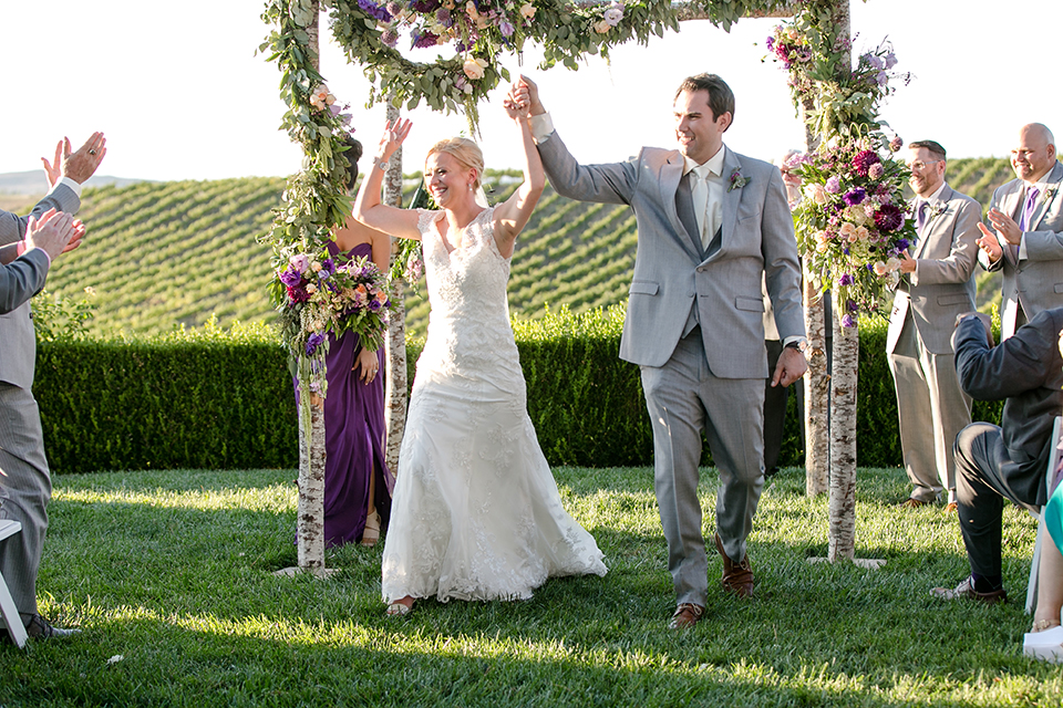Temecula outdoor wedding at callaway winery bride form fitting lace gown with sheer back design and high neckline with groom heather grey notch lapel suit with matching vest and white dress shirt with long white tie and light purple floral boutonniere cheering after ceremony