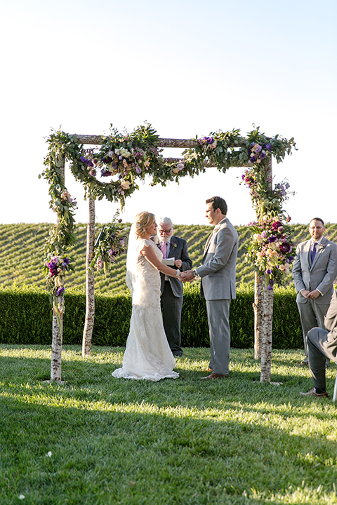 Temecula outdoor wedding at callaway winery bride form fitting lace gown with sheer back design and high neckline with groom heather grey notch lapel suit with matching vest and white dress shirt with long white tie and light purple floral boutonniere holding hands during ceremony