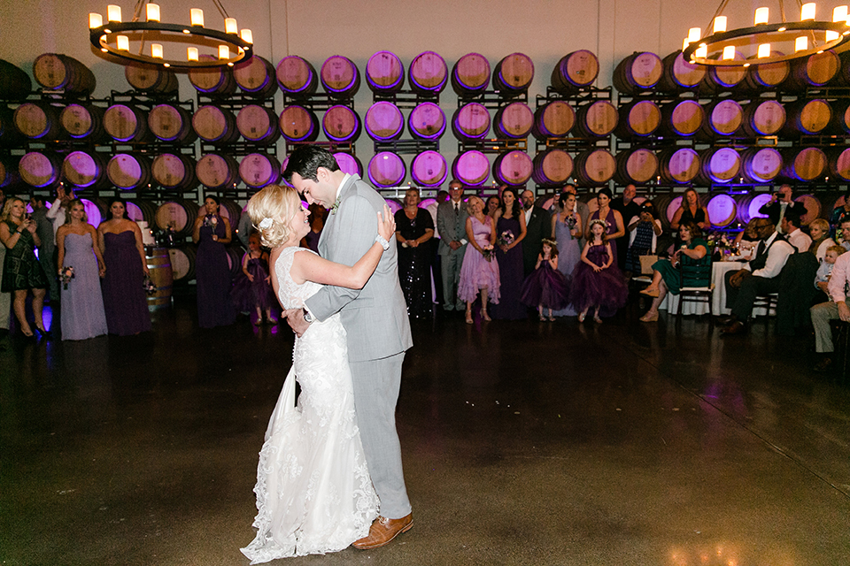 Temecula outdoor wedding at callaway winery bride form fitting lace gown with sheer back design and high neckline with groom heather grey notch lapel suit with matching vest and white dress shirt with long white tie and light purple floral boutonniere first dance