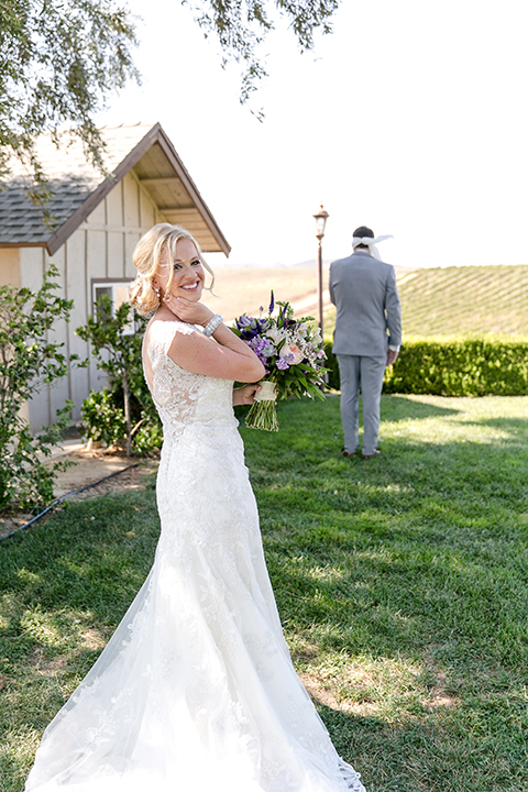 Temecula outdoor wedding at callaway winery bride form fitting lace gown with sheer back design and high neckline with groom heather grey notch lapel suit with matching vest and white dress shirt with long white tie and light purple floral boutonniere first look