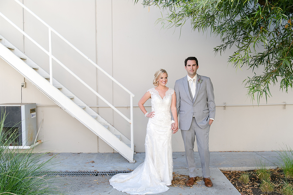 Temecula outdoor wedding at callaway winery bride form fitting lace gown with sheer back design and high neckline with groom heather grey notch lapel suit with matching vest and white dress shirt with long white tie and light purple floral boutonniere holding hands