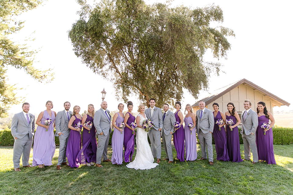 Temecula outdoor wedding at callaway winery bride form fitting lace gown with sheer back design and high neckline with groom heather grey notch lapel suit with matching vest and white dress shirt with long white tie and light purple floral boutonniere with wedding party bridesmaids long purple dresses different shades and groomsmen heather grey suits with purple ties