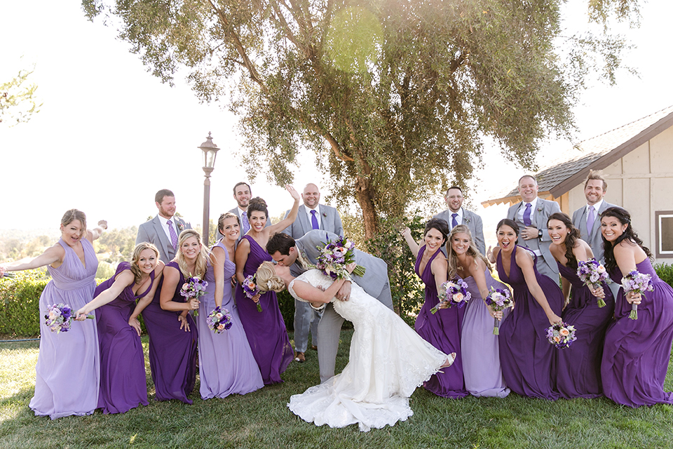 Temecula outdoor wedding at callaway winery bride form fitting lace gown with sheer back design and high neckline with groom heather grey notch lapel suit with matching vest and white dress shirt with long white tie and light purple floral boutonniere with wedding party kissing and cheering bridesmaids long purple dresses different shades and groomsmen heather grey suits with long purple ties