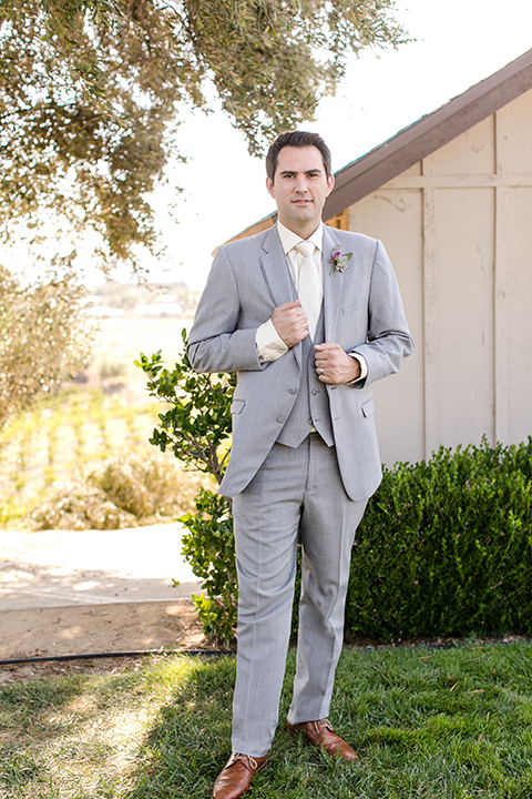 Temecula outdoor wedding at callaway winery groom heather grey notch lapel suit with a matching vest and white dress shirt with a long white tie and light purple floral boutonniere standing holding jacket