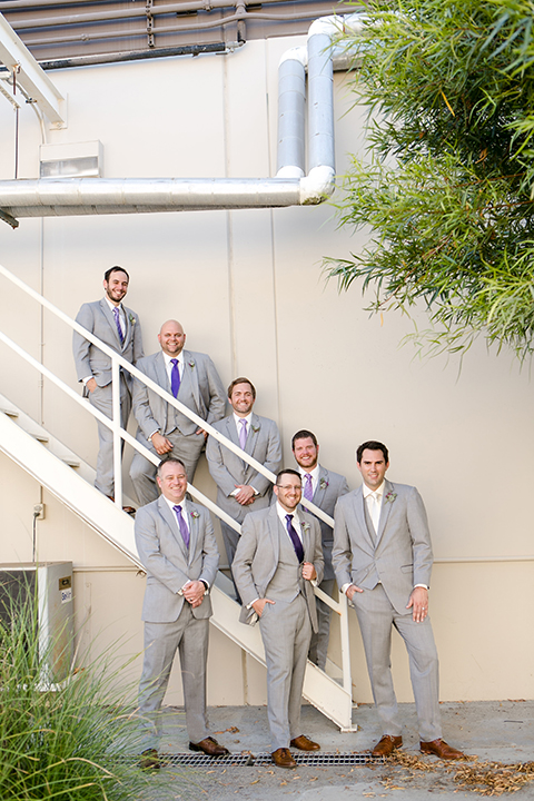 Temecula outdoor wedding at callaway winery groom heather grey notch lapel suit with matching vest and white dress shirt with a long white tie and light purple floral boutonniere standing with groomsmen heather grey suits with long purple ties