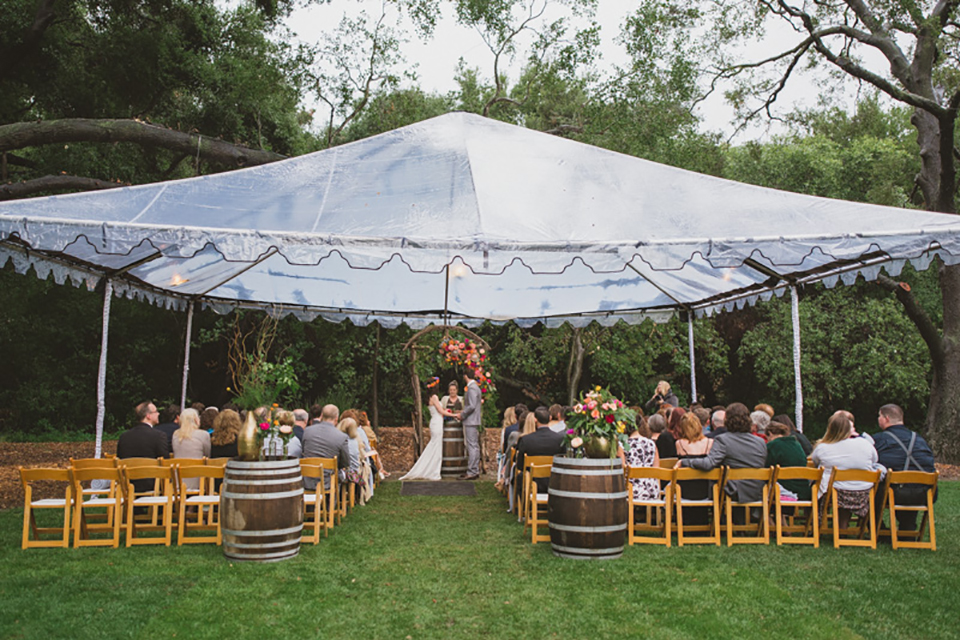Temecula outdoor wedding at temecula creek inn bride form fitting simple strapless gown with a straight neckline and teal rain boots with groom grey notch lapel suit with a white dress shirt and long brown tie with an orange floral boutonniere holding hands during ceremony