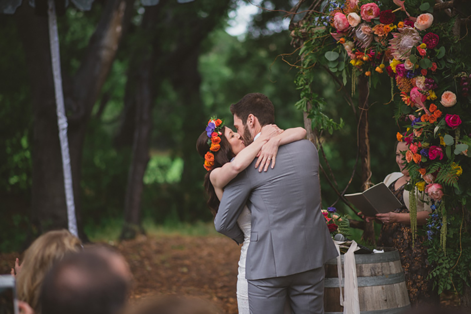 Temecula outdoor wedding at temecula creek inn bride form fitting simple strapless gown with a straight neckline and teal rain boots with groom grey notch lapel suit with a white dress shirt and long brown tie with an orange floral boutonniere kissing during ceremony close up