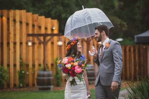 Temecula outdoor wedding at temecula creek inn bride form fitting simple strapless gown with a straight neckline and teal rain boots with groom grey notch lapel suit with a white dress shirt and long brown tie with an orange floral boutonniere standing under clear umbrella bride holding colorful floral bridal bouquet