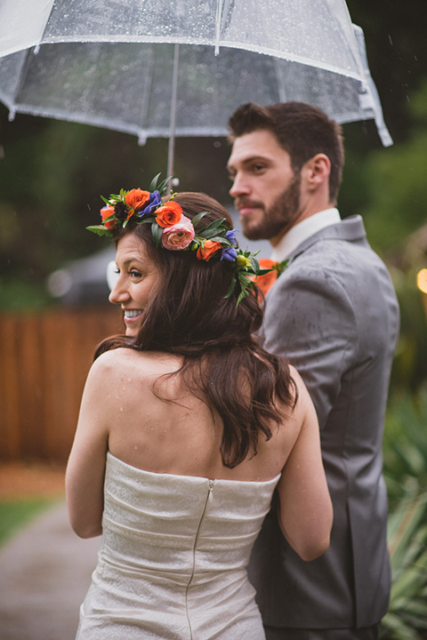 Temecula outdoor wedding at temecula creek inn bride form fitting simple strapless gown with a straight neckline and teal rain boots with groom grey notch lapel suit with a white dress shirt and long brown tie with an orange floral boutonniere hugging and holding clear umbrella