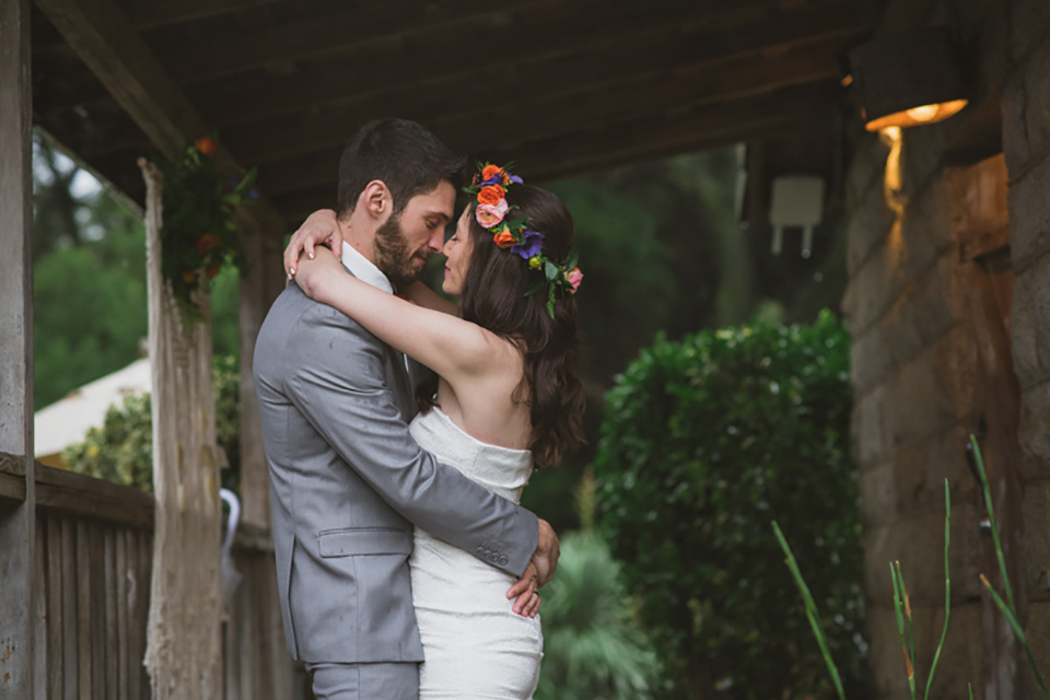 Temecula outdoor wedding at temecula creek inn bride form fitting simple strapless gown with a straight neckline and teal rain boots with groom grey notch lapel suit with a white dress shirt and long brown tie with an orange floral boutonniere hugging and bride wearing colorful floral crown