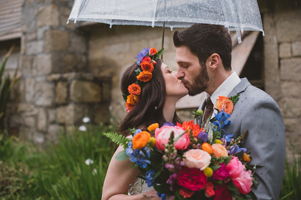 Temecula outdoor wedding at temecula creek inn bride form fitting simple strapless gown with a straight neckline and teal rain boots with groom grey notch lapel suit with a white dress shirt and long brown tie with an orange floral boutonniere kissing under clear umbrella bride holding colorful floral bridal bouquet and wearing matching floral crown