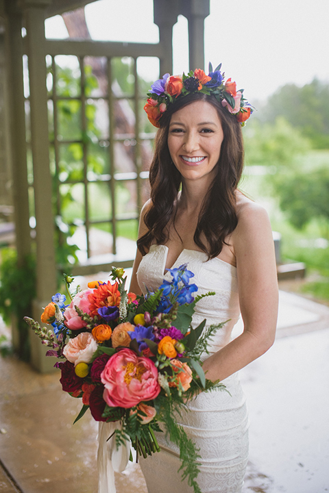 Temecula outdoor wedding at temecula creek inn bride form fitting simple strapless gown with a straight neckline and teal rain boots wearing colorful floral crown holding colorful floral bridal bouquet